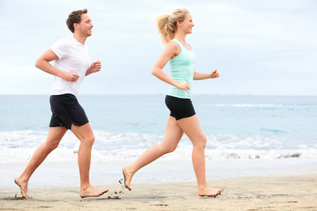 Couple running outdoors on beach  Woman and man runners jogging together outside in full body length  photo