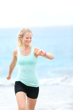 Running woman jogger looking at heart rate monitor watch outside jogging on beach  Female fitness runner girl jogger training outdoors listening to music in earphones  Beautiful young blonde woman in her 20s  photo