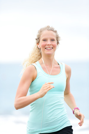 resting heart rate: Jogging woman running woman outside on beach  Female fitness runner girl jogger training outdoors listening to music in earphones  Beautiful young blonde woman in her 20s