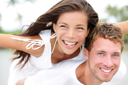 Happy couple on beach having fun piggyback ride in love outdoor smiling happy laughing together on romantic holidays vacation travel trip. Young multiracial people, Asian woman, Caucasian man, 20s. photo