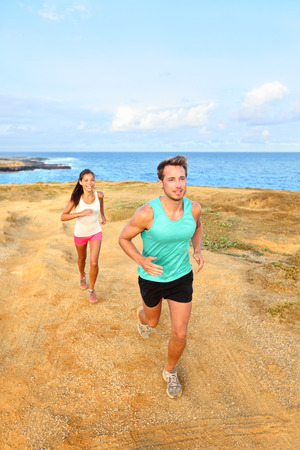Runners running outside by ocean. Runner couple athletes, man and woman jogging outdoors in beautiful landscape on Green Sand Beach, Papakolea on Big Island, Hawaii, USA. photo