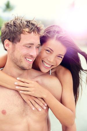 Šťastný romantický pár milenci na pláži líbánky s hravou zábavu spolu během letních dovolenou u moře. Veselý mladý mnohonárodnostní pár, asijské ženy a muž běloch ve svých dvaceti let.