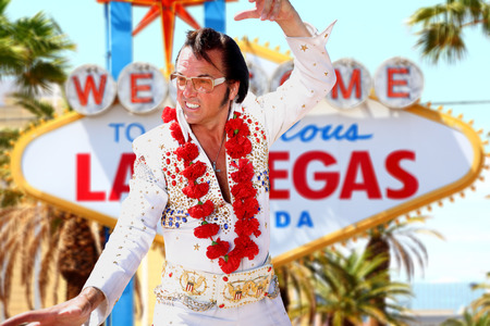 lookalike: Elvis look-alike impersonator man and Las Vegas sign on the strip. People having fun and Viva Las Vegas concept image with Elvis impersonator dancing doing some crazy moves outdoor. Editorial