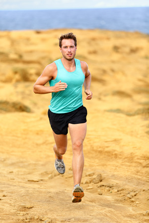 Running athlete man. Male runner cross country running and jogging training on trail outdoors on Big Island, Hawaii, USA photo