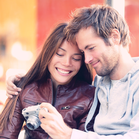 couple having fun: Couple looking at pictures on camera. Beautiful young lovers having fun together outside looking at photos on vintage retro camera. Interracial couple, Asian woman, Caucasian man.