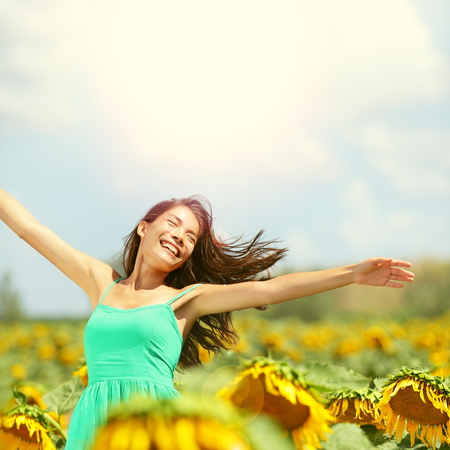 Happy woman in sunflower field. Summer girl in flower field cheerful and joyful. Multiracial Asian Caucasian young woman dancing, smiling elated and serene with arms raised up. photo