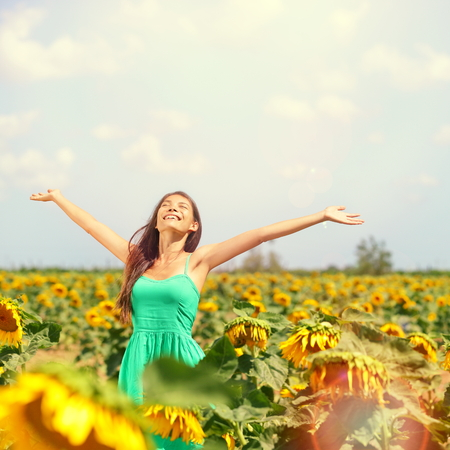 Woman summer girl happy in sunflower flower field. Cheerful multiracial Asian Caucasian young woman joyful, smiling with arms raised up. 写真素材