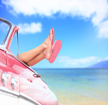 Woman legs by blue sea background in car. Summer vacations concept with free woman enjoying freedom. Stock Photo