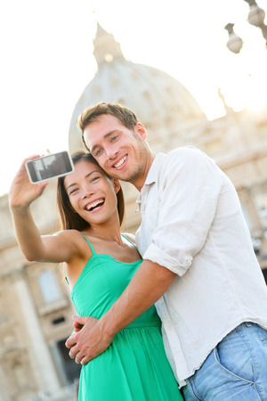 Tourists couple selfie by Vatican city and St. Peters Basilica church in Rome. Happy travel woman and man taking selfie photo picture on romantic honeymoon in Italy. photo