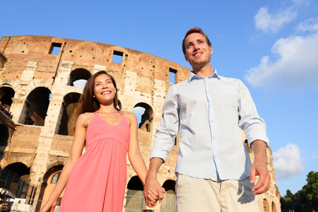 Couple in Rome by Colosseum walking holding hands in Italy. Happy lovers on honeymoon sightseeing having fun in front of Coliseum. Love and travel concept with multiracial couple. photo