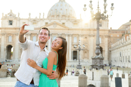 Tourists couple by Vatican city and St. Peters Basilica church in Rome. Happy travel woman and man taking selfie photo picture on romantic honeymoon in Italy.