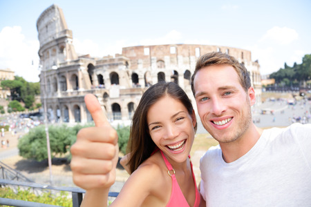 Selfie - Romantic travel couple by Coliseum, Rome, Italy. Happy lovers on honeymoon sightseeing having fun in front of Colosseum. Woman giving thumbs up in tourism travel concept. Stock Photo