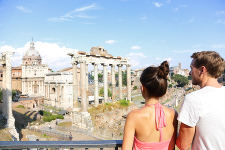 Roman Forum tourists looking at landmark in Rome sightseeing on travel vacation in Rome, Italy. Happy tourist couple, man and woman traveling on holidays in Europe smiling happy.