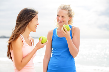 Healthy lifestyle women eating apple after running. Two beautiful girlfriends talking enjoying fruit after jogging training on beach. Caucasian woman and Asian woman in their 20s smiling happy. photo