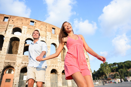 Travel Couple in Rome by Colosseum running fun and romantic holding hands in Italy. Happy lovers on honeymoon sightseeing having fun by Coliseum. Love and travel concept with multiracial couple.