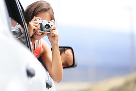 Woman tourist taking photo in car with camera driving on road trip travel vacation. Girl passenger taking picture out of window with vintage retro camera. Stock Photo