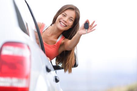 Auto bestuurder vrouw die gelukkig met autosleutels uit raam. Nieuwe auto, huur of rijbewijs concept met jonge vrouwelijke model op road trip. Gemengd ras Aziatische Kaukasische meisje in haar jaren '20.