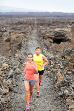 Cross country running woman and man trail runners jogging training outdoors for marathon or triathlon run in beautiful volcano landscape nature. Athlete couple working out on Big Island, Hawaii. photo