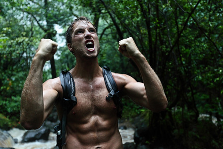 Muscular survivor man in jungle rainforest cheering aggressive. Strong male survival concept with guy celebrating cheerful in forest at night showing muscles and aggressive survival instincts. photo