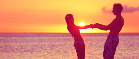 Happy woman and man holding hands playful in romance in beautiful sun light photo