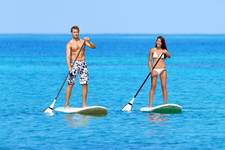 sup: Stand up paddleboarding beach people on stand up paddle board, SUP surfboard surfing in ocean sea on Big Island, Hawaii Beautiful young mixed race Asian woman and Caucasian man doing water sport.