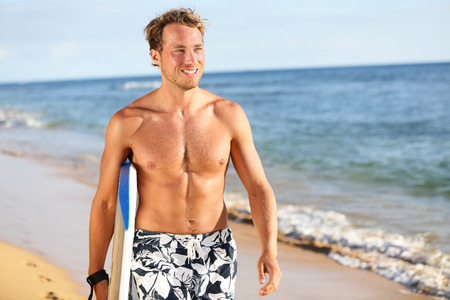 boogie: Surfer fun on summer beach - handsome man. Bodyboarding surfing good looking fit fitness model running with bodyboard surfboard during vacation holidays getaway. Caucasian male model in his 20s. Stock Photo