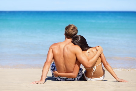 Romantic beach couple in love relaxing on vacation enjoying ocean view together sitting in the sand embracing and hugging. Beautiful young multiracial couple, Asian woman, Caucasian man. photo