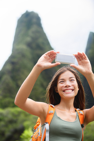 hikers: Woman hiker taking selfie photo using smartphone while hiking on Hawaii enjoying outdoor activity. Woman hiker taking photo with smart phone camera. Iao Valley State Park, Wailuku, Maui, USA.