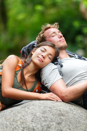 Hiking couple lovers relaxing sleeping in nature. Tried hikers resting lying down outdoors taking a break from hike. Young Asian woman and Caucasian man. photo