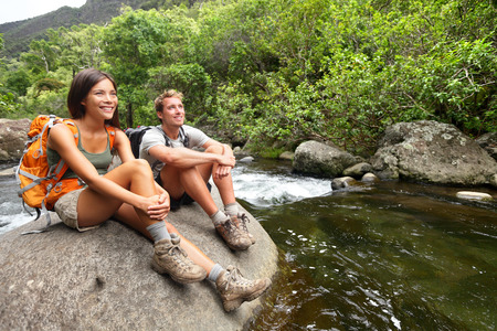 state park: Hiking couple of hikers in outdoor activity wearing backpacks relaxing. Woman and man hiker looking with smiling happy. Healthy lifestyle image from Iao Valley State Park, Wailuku, Maui, Hawaii, USA.