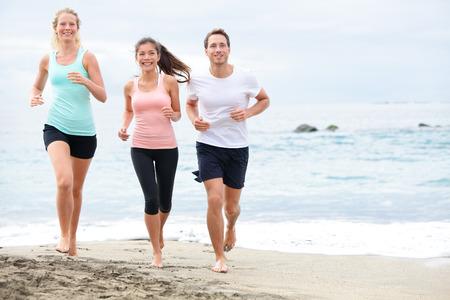 Hardlopen vrienden op het strand joggen groepstraining. Het uitoefenen lopers training buiten leven gezond actieve levensstijl. Multiraciale fitness runner mensen werken samen buiten glimlachen gelukkig. Stockfoto
