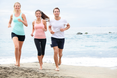 Running friends on beach jogging group training. Exercising runners training outdoors living healthy active lifestyle. Multiracial fitness runner people working out together outside smiling happy. photo
