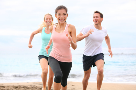 joggers: Multiracial fitness runner people working out together outside smiling happy. Stock Photo