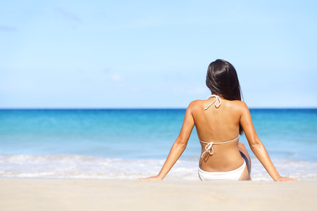 Woman on beach sitting in sand looking at ocean enjoying sun and summer travel holidays vacation getaway. Girl in bikini relaxing under blue sky. photo