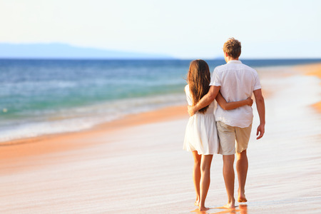 in behind: Beach couple walking on romantic travel honeymoon vacation summer holidays romance Stock Photo
