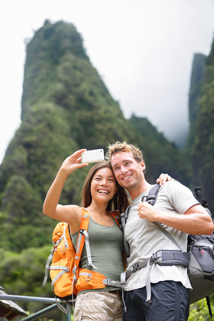 taking: Couple taking selfie self portrait hiking on Hawaii in outdoor activity