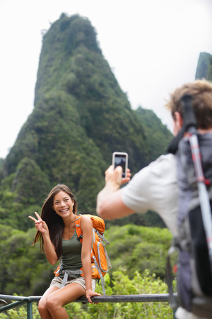 Couple taking photos having fun lifestyle hiking on Hawaii in outdoor activity. Woman and man hiker taking photo pictures with smart phone camera. Iao Valley State Park, Wailuku, Maui, USA. photo