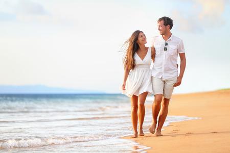 romance: ビーチのカップルはロマンチックな旅行新婚旅行休暇夏の休日のロマンスの上を歩いてします。若い幸せな恋人、アジアの女性と屋外を受け入れる
