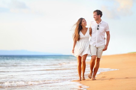 Beach couple walking on romantic travel honeymoon vacation summer holidays romance. Young happy lovers, Asian woman and Caucasian man holding hands embracing outdoors.