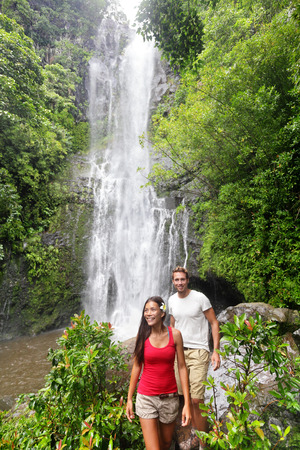 couple in rain: Hawaii tourist hiking people. Couple happy by waterfall during travel on the road to Hana on Maui, Hawaii. Ecotourism concept image with happy backpackers. Interracial Asian  Caucasian young couple. Stock Photo