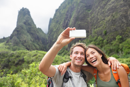 traveller: Couple taking selfie photo with smart phone hiking on Hawaii. Woman and man hiker taking photo with smart phone camera. Healthy lifestyle from Iao Valley State Park, Wailuku, Maui, Hawaii, USA.