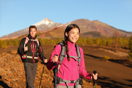 People hiking - healthy active lifestyle couple. Hikers walking in beautiful mountain nature landscape. Woman and man hikers walking during hike on volcano Teide, Tenerife, Canary Islands, Spain. photo
