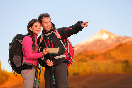 Tablet PC - hiking couple using travel app or map on hike. Man and woman hikers looking at view pointing and showing during hike on volcano Teide, Tenerife, Canary Islands, Spain. photo