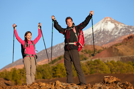 Success winning celebrating hiking people at top. Cheering hiker couple enjoying freedom on hike with arms raised in mountain landscape. Woman and man on volcano Teide, Tenerife, Canary Islands, Spain photo