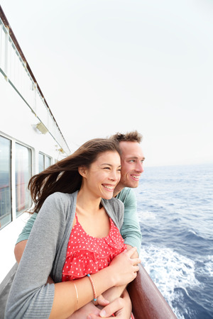 Romantic couple on cruise ship enjoying travel on boat embracing looking at view. Happy lovers traveling on vacation sailing on open sea ocean enjoying romance. Young Asian woman and Caucasian man. photo