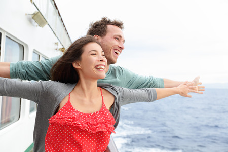 titanic: Romantic couple having fun laughing in funny pose on cruise ship boat. Smiling happy man and woman on travel vacation holidays on open ocean sea.