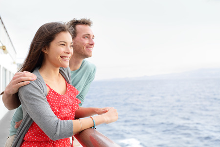 Romantic happy couple on cruise ship on boat travel embracing looking at view. Happy lovers traveling on vacation sailing on open sea ocean enjoying romance. Young Asian woman and Caucasian man. Stock Photo