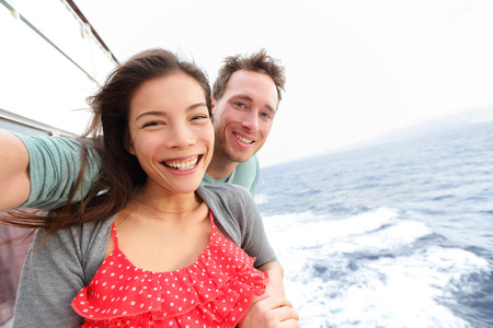 Cruise ship couple taking selfie self portrait photo romantic. Happy lovers, woman and man traveling on vacation travel sailing on open sea ocean enjoying romance. Young Asian woman and Caucasian man. photo