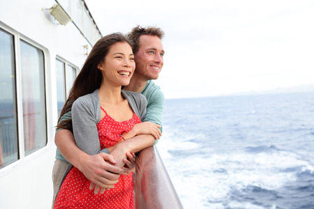 Cruise ship couple romantic enjoying travel on boat embracing looking at view. Happy lovers traveling on vacation sailing on open sea ocean enjoying romance. Young Asian woman and Caucasian man. photo