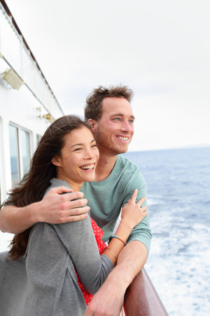 Cruise ship couple romantic on boat embracing looking at view. Happy lovers, woman and man traveling on vacation travel sailing on open sea ocean enjoying romance. Young Asian woman and Caucasian man. photo